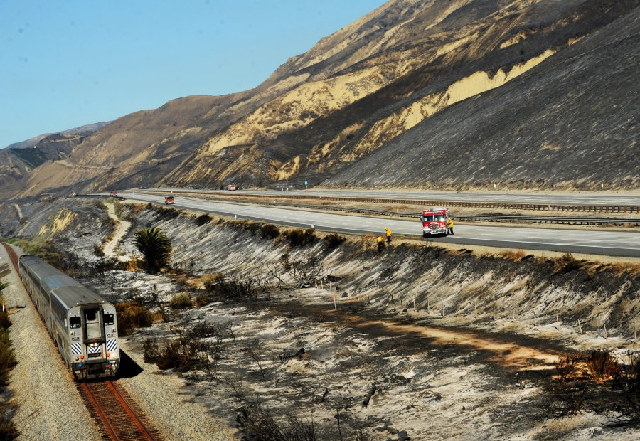 A train passes a burned segment of hillside e along PCH just North of Ventura, Boxing Day, 2015 (Image: Chuck Kirman/Ventura County Star).