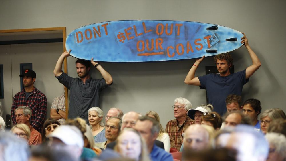 Alex Lowe, left, and Rob Moddlemog from Orange County hold a surf board as members of the California Coastal Commission listen to speakers in support of Charles Lester.  Image: Al Seib/Los Angeles Times.